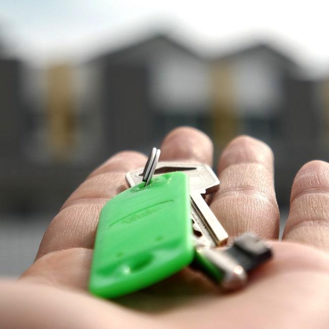 Auf einer ausgestreckten Handfläche liegt ein Schlüsselbund.