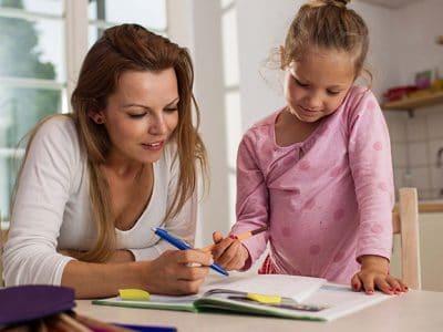 Frau hilft Mädchen bei den Schulaufgaben
