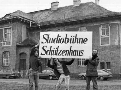 """Drei junge Männer halten ein Schild hoch, auf dem """"Studiobühne Schützenhaus"""" steht."""