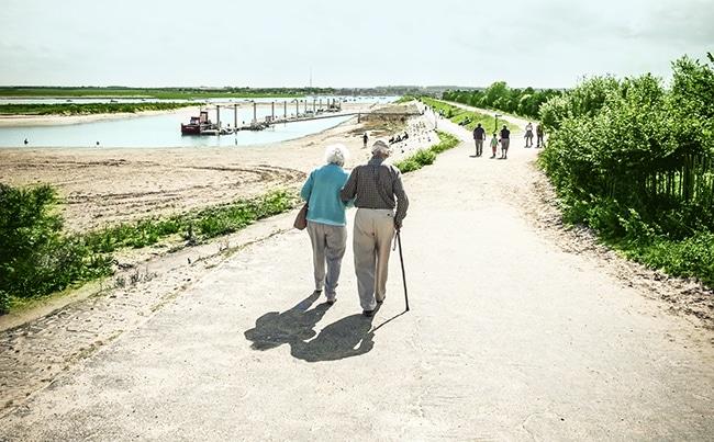Ein älteres Paar läuft einen Weg entlang