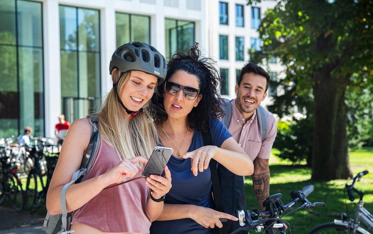 Zwei junge Frauen mit Fahrrad schauen aufs Handy. Foto: Laura Nickel