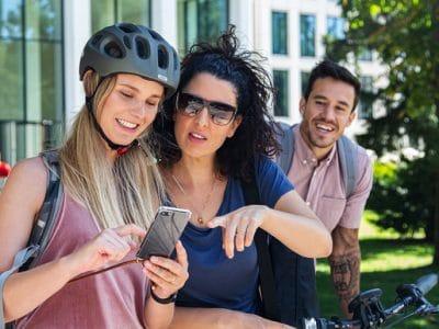 Zwei junge Frauen mit Fahrrad schauen auf ein Handy.
