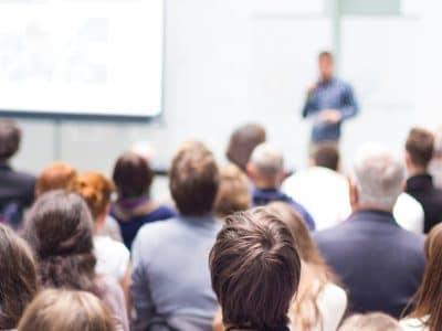 Beispielbild. Publikum blickt auf einen Vortragenden