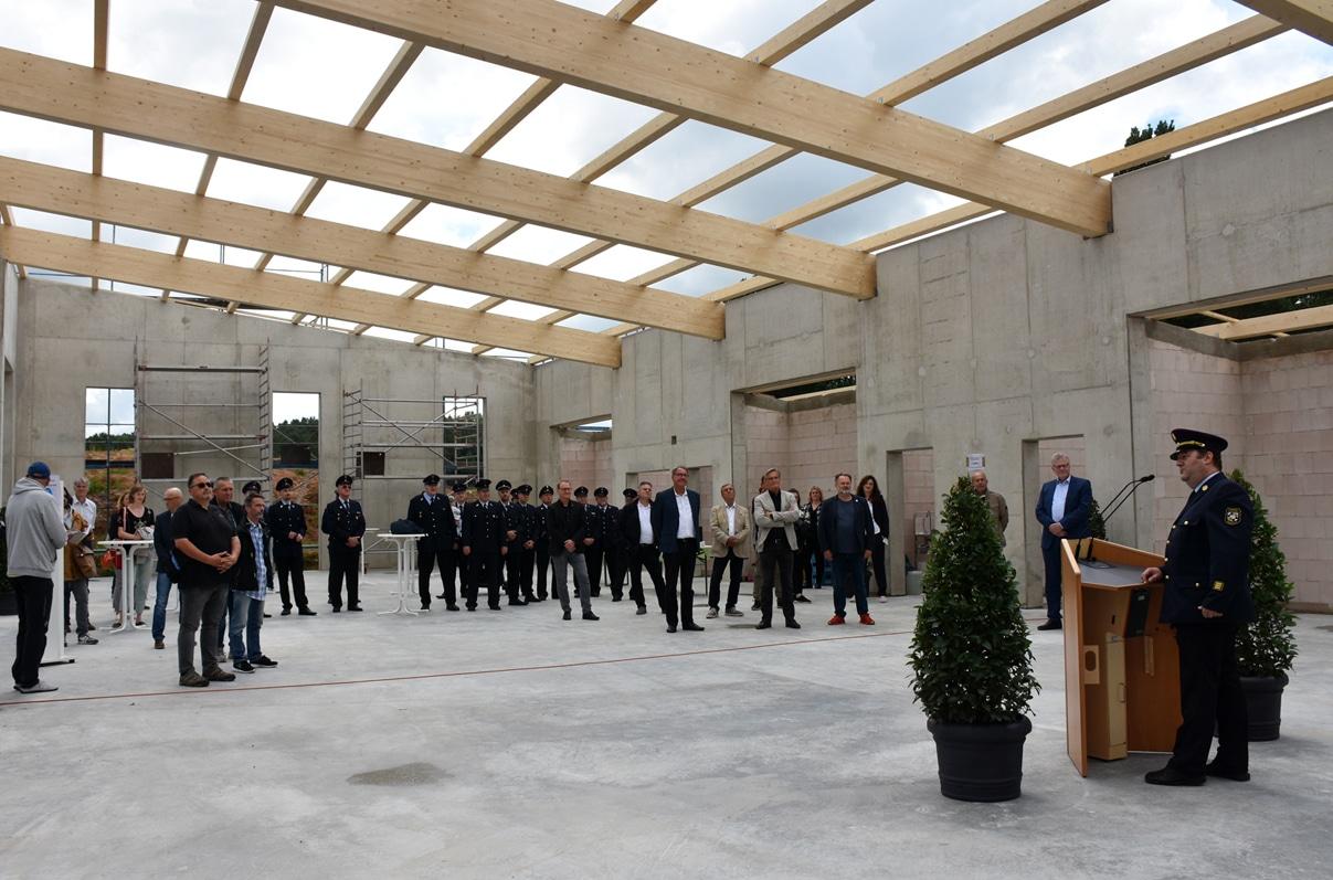 Gäste des Richtfestes stehen im Rohbau des neuen Feuerwehrgerätehauses Süd. | Foto: Andreas Türk