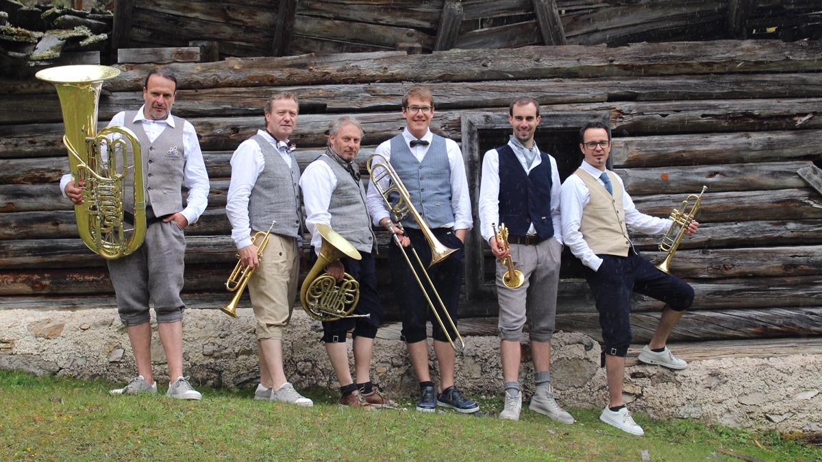 Die sechs Musiker von Brozen Brass vor einer Almhütte.