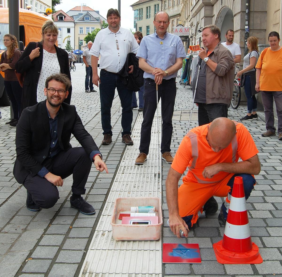 Mehrere Menschen schauen einem Mitarbeiter des Stadtbauhofs zu, wie er das Logo des Blindenleitsystems auf den Boden sprüht.