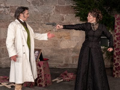 """Szene aus """"Der Bär"""": Eine Frau bedroht einen Mann mit der Pistole."""