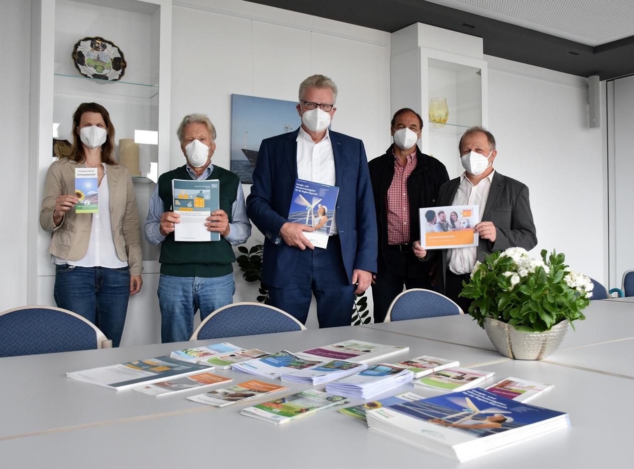 Vier Männer und Frauen präsentieren Broschüren.