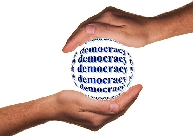 zwei Hände halten eine Kugel, auf der democracy steht
